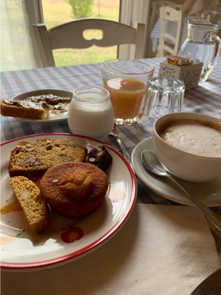 Piatto di dolci per colazione, bicchiere di spremuta e tazza di cappuccino su una tovaglia a quadretti bianchi e azzurri