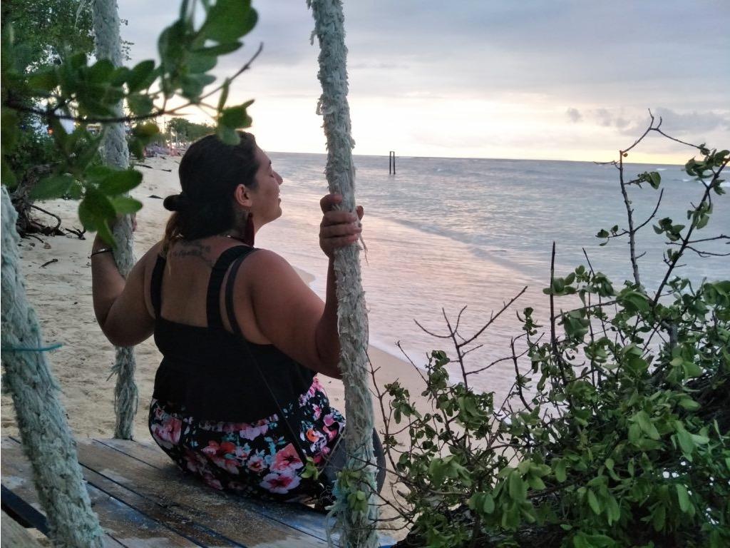 Ragazza su un'altalena in spiaggia al tramonto