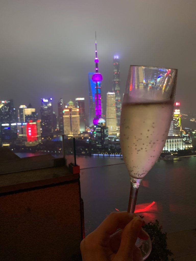 Calice di prosecco in primo piano, sullo sfondo i grattacieli di Shanghai illuminati di notte