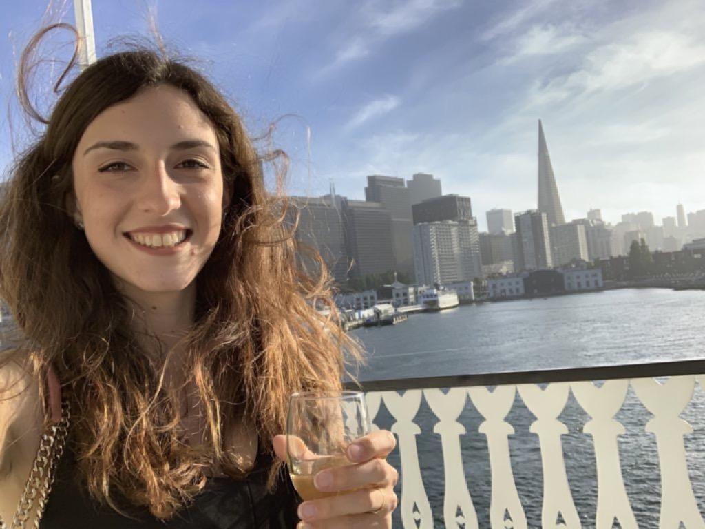 Ragazza con calice di spumante su un traghetto nella baia di San Francisco, con sfondo grattacieli