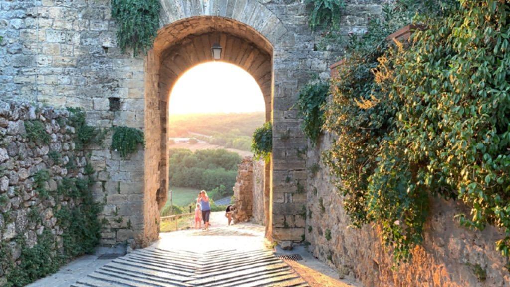 Una delle porte di Monteriggioni da cui si intravede il tramonto sui campi
