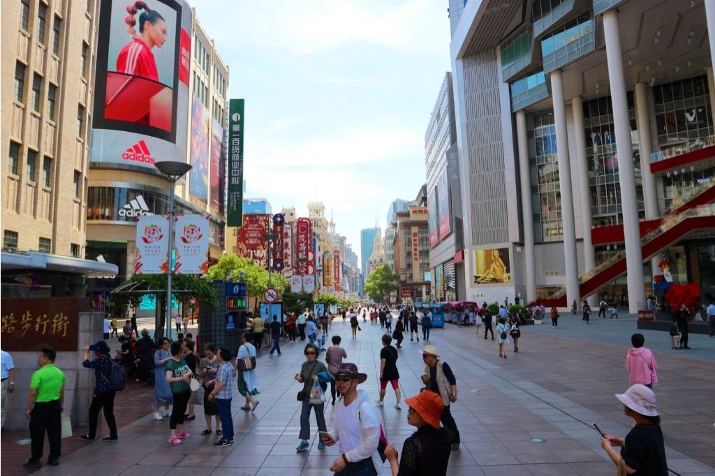 Via affollata di Shanghai di giorno, con negozi e centri commerciali e insegne colorate