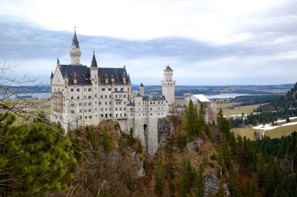 Veduta laterale di un castello bianco con tetti blu, costruito su una rocca in mezzo ad alberi