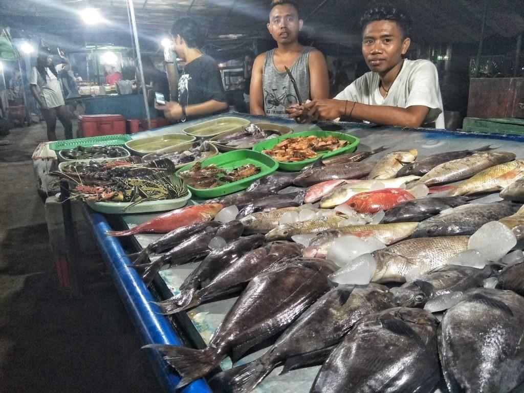 Indonesiani che vendono il pesce al Night Market