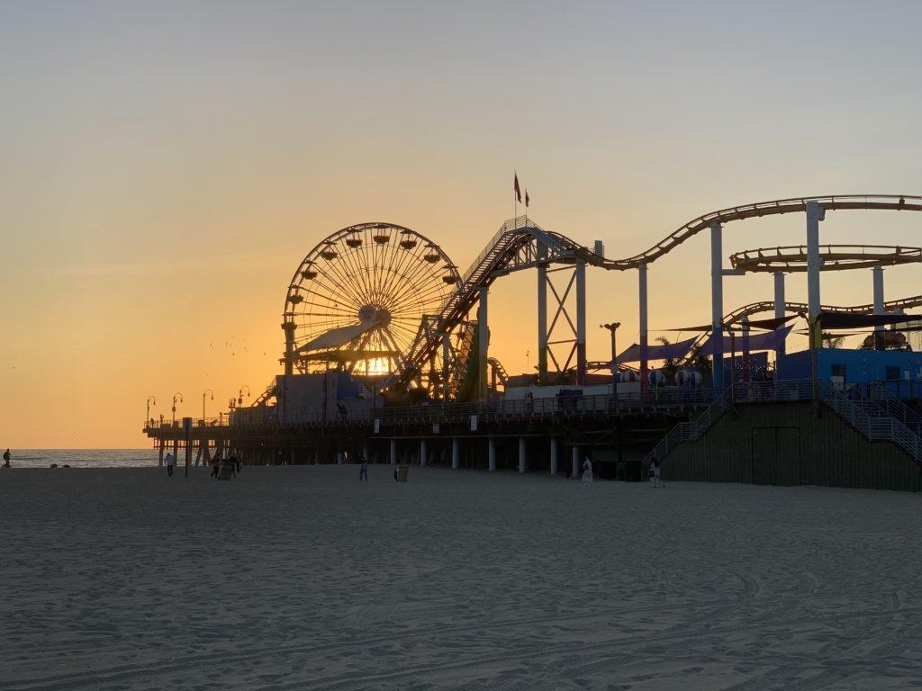 Tramonto sulla spiaggia dietro alla ruota panoramica e alle giostre del Santa Monica Pier