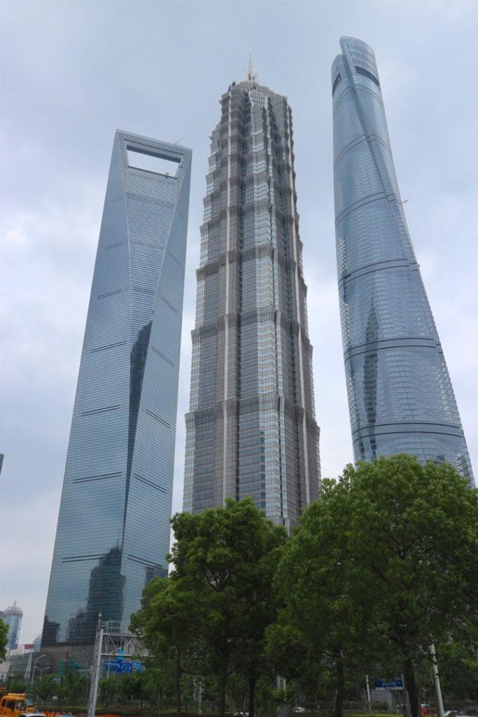 Tre grattacieli di Shanghai visti dal basso con cielo nuvoloso e grigio