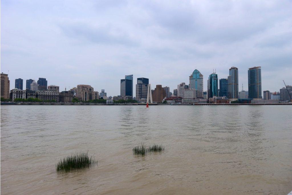 Fiume con acqua marroncina, in fondo edifici della città e cielo grigio