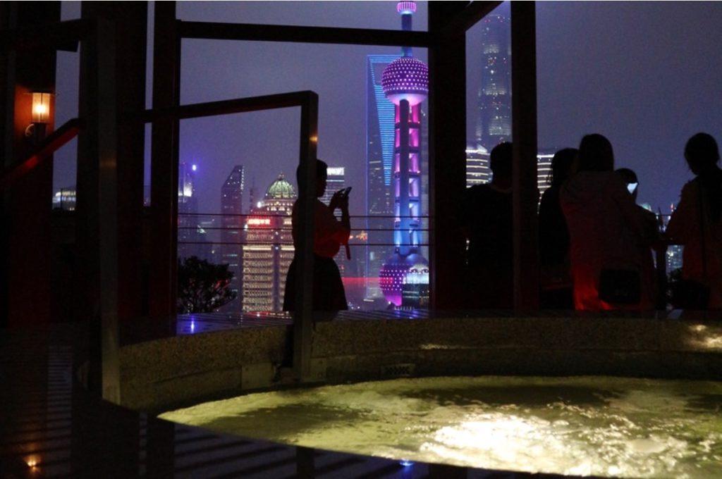 Primo piano di una Jacuzzi illuminata di notte, su una terrazza con vista sui grattacieli di Shanghai, con sagome nere di persone
