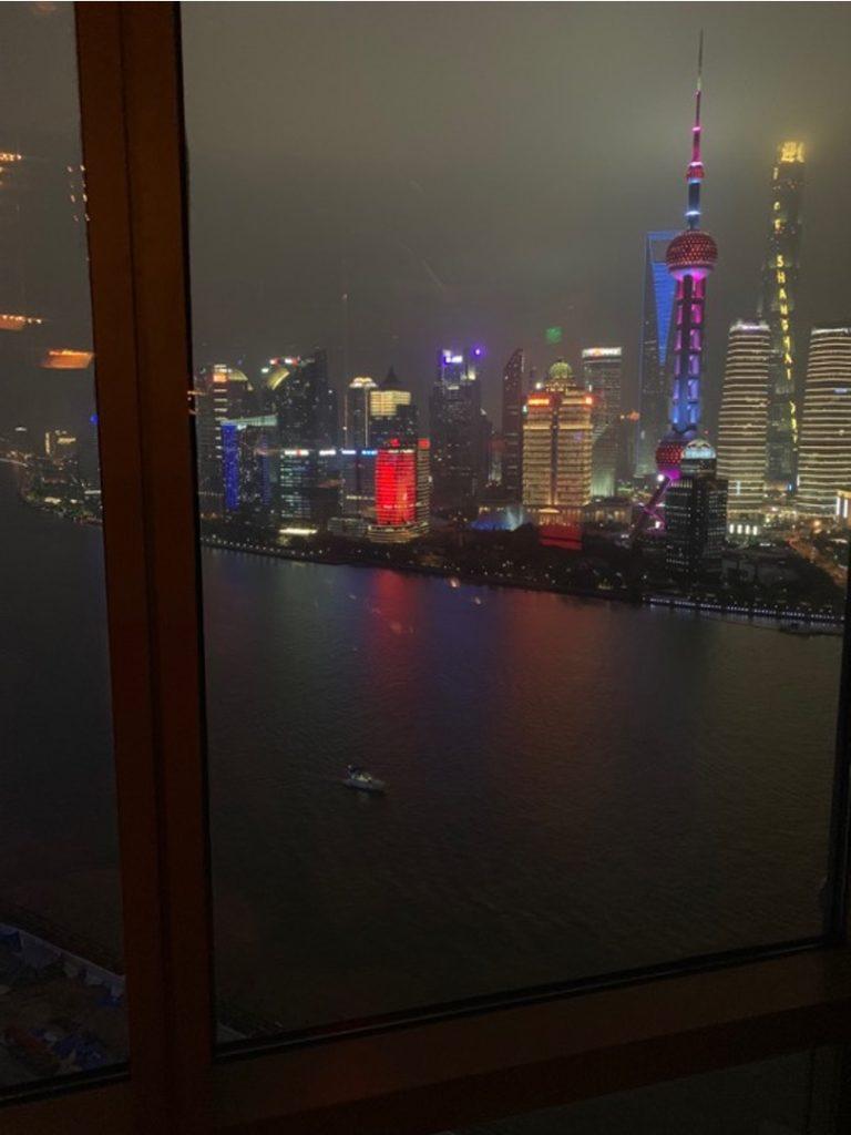 Vista sui grattacieli illuminati di Shanghai da una vetrata di un palazzo