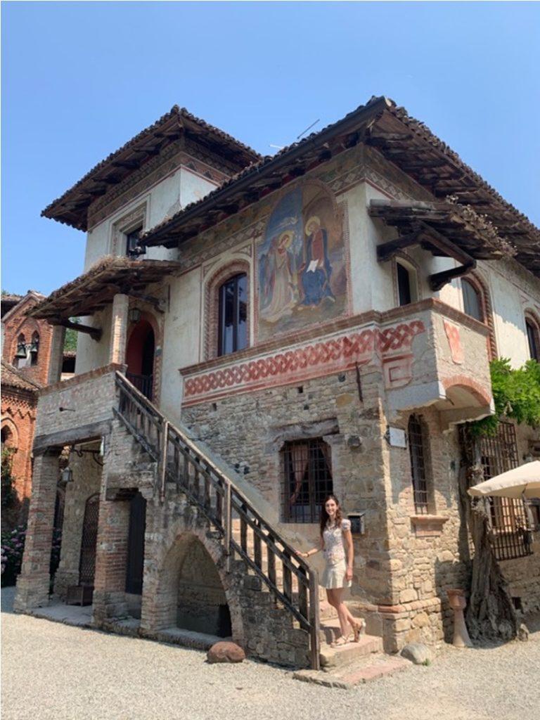 Ragazza sulle scale di un edificio affrescato in un borgo medievale