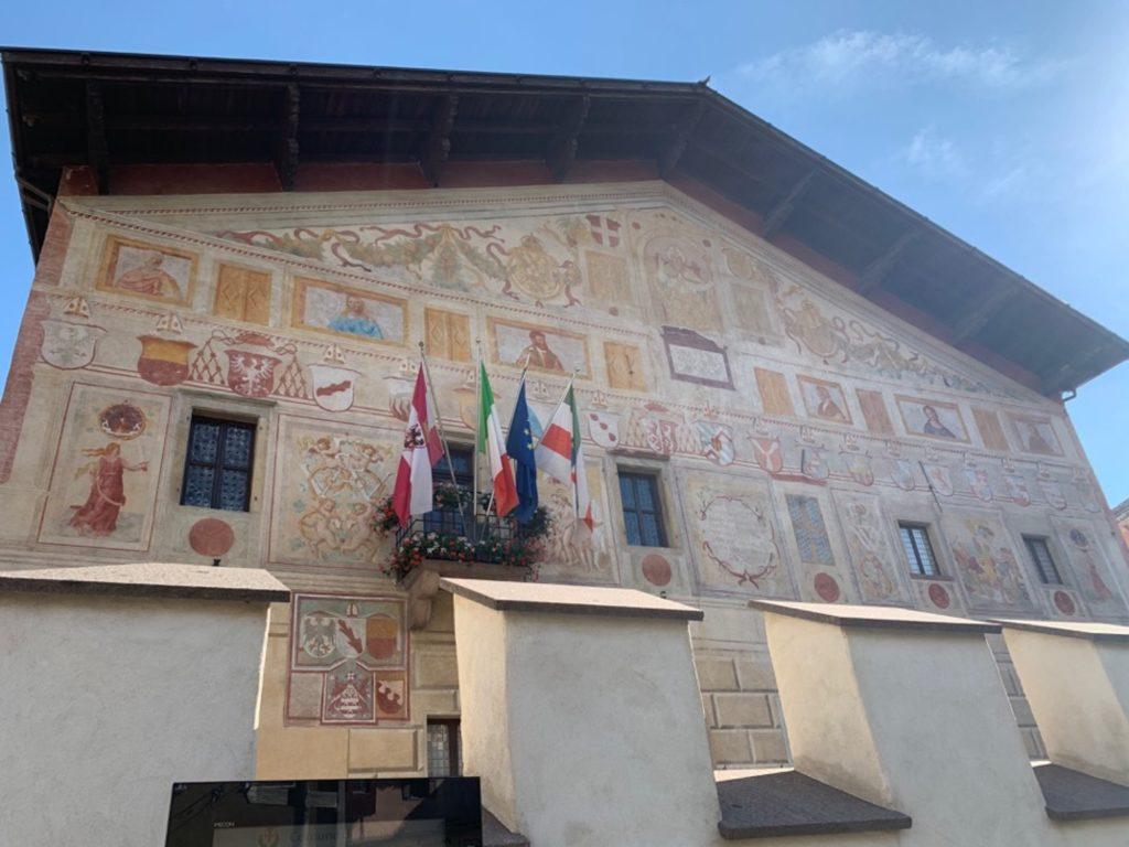 Palazzo affrescato con bandiere a una finestra