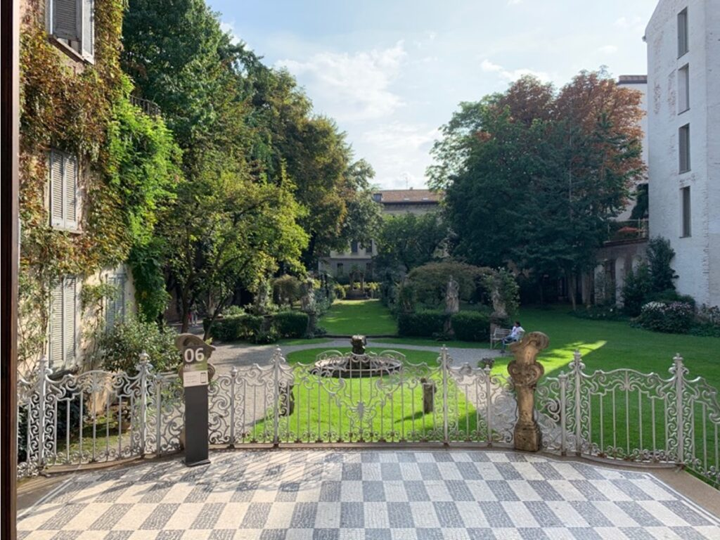 Un balcone che si affaccia su un elegante giardino con alberi e fontana