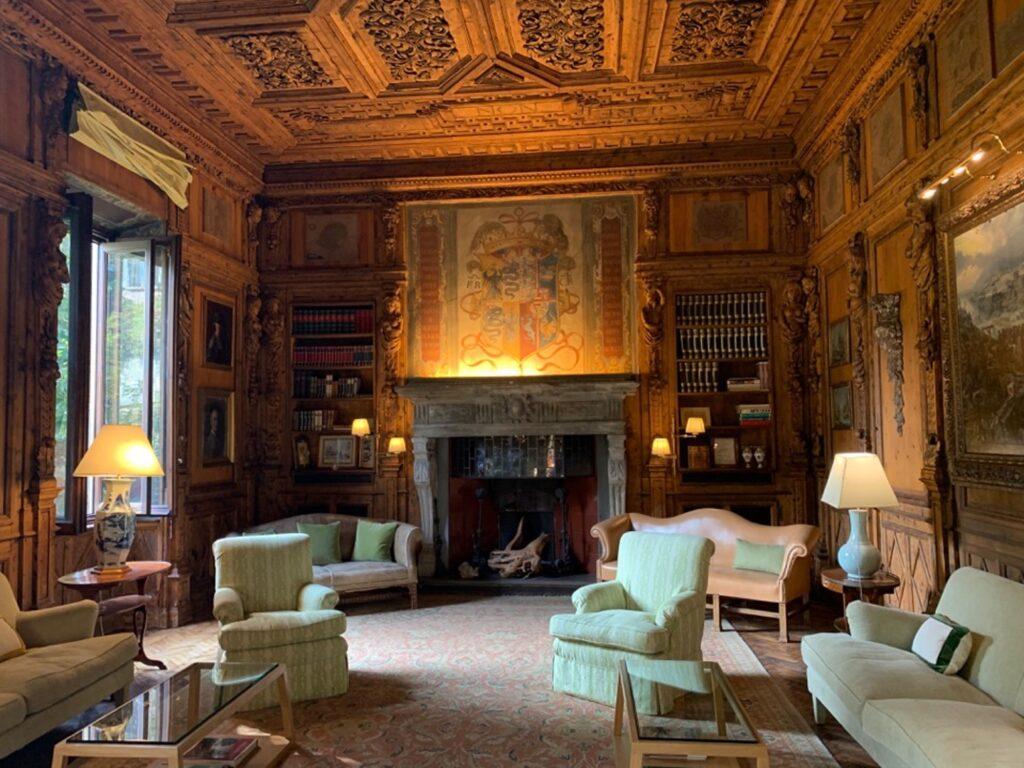 Una stanza adibita a studio, con grande camino, pareti in legno, librerie e poltrone antiche