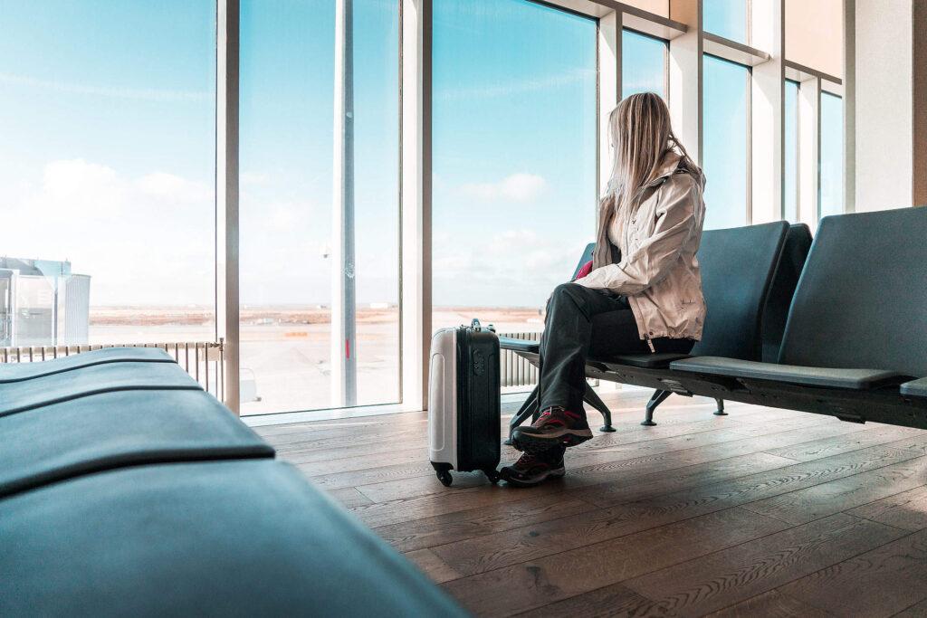 Una ragazza aspetta il suo volo seduta in aeroporto con davanti una piccola valigia