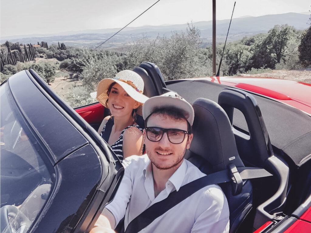 Ragazzo e ragazza in una macchina spider in Toscana