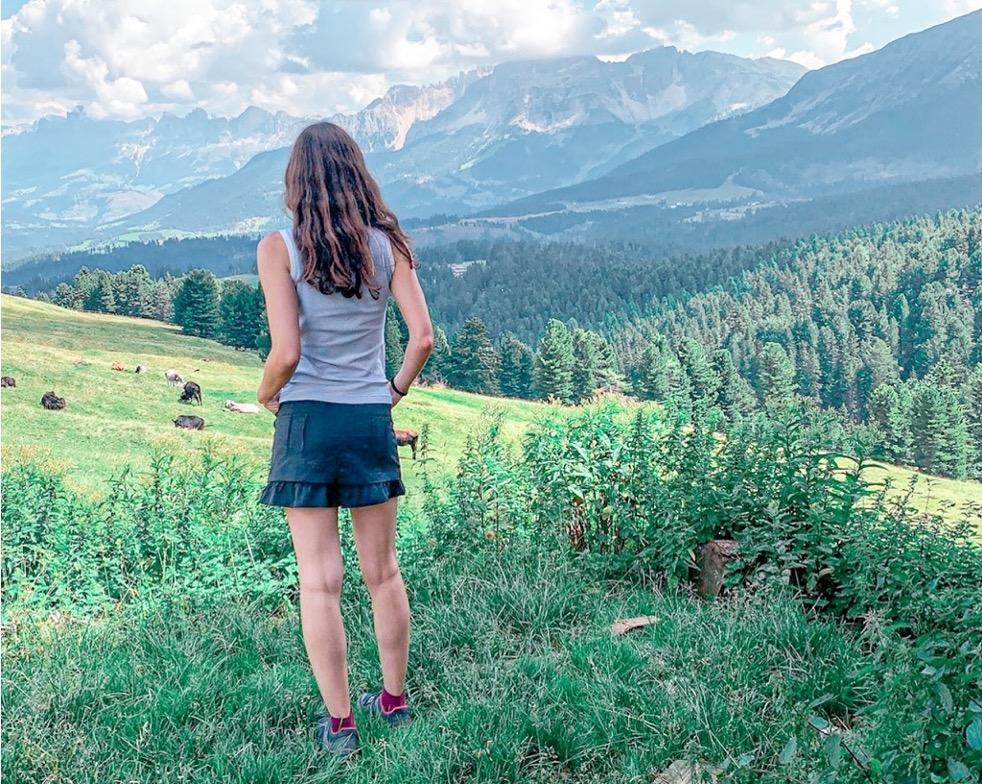 Ragazza di spalle in un prato che guarda le montagne