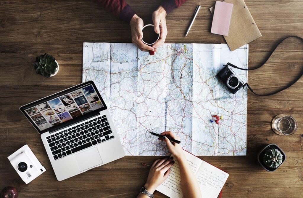 Una cartina su un tavolo e due persone che organizzano il prossimo viaggio