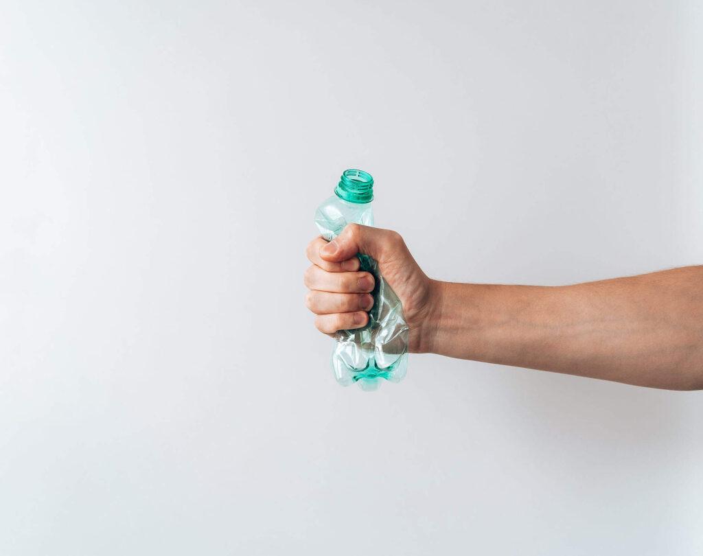 Una mano stringe e rompe una bottiglietta di plastica